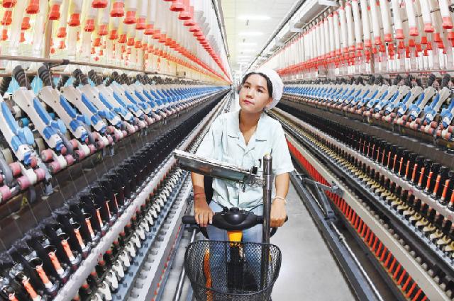 Мархаба Вулайим, 25 лет, прядильщица из уезда Шулэ, округ Кашгар, Синьцзян-Уйгурский автономный район, проверяет оборудование на местной текстильной фабрике.