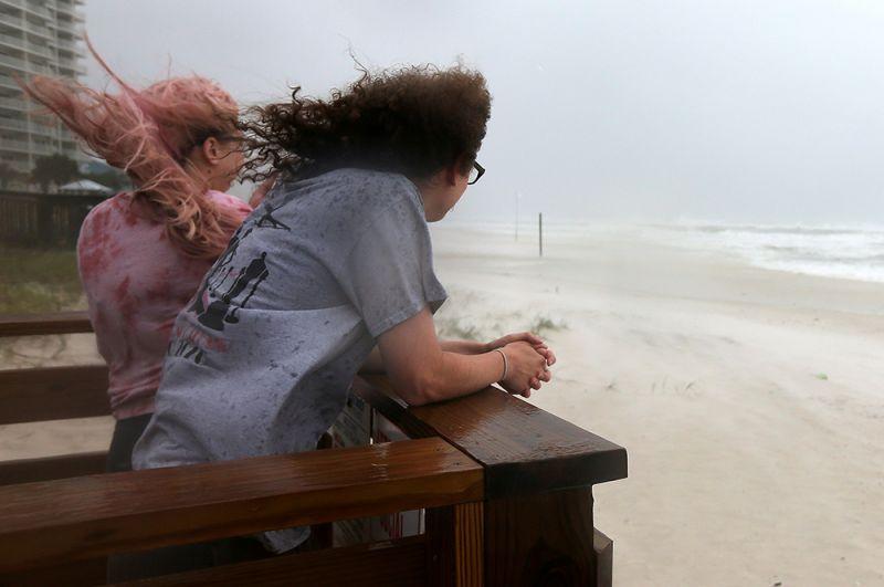 Пара наблюдает за приближением шторма на пляже Орандж-Бич, штат Алабама.