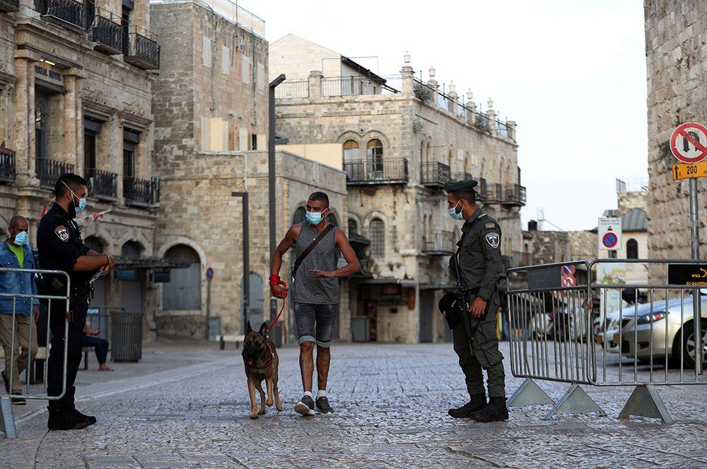 При этом запрещено ходить в гости, отдыхать на пляжах, собираться компаниями более 10 человек в закрытых помещениях и более 20 человек на открытых пространствах. На фото: полицейские на контрольно-пропускном пункте рядом с Яффскими воротами в Иерусалим.
