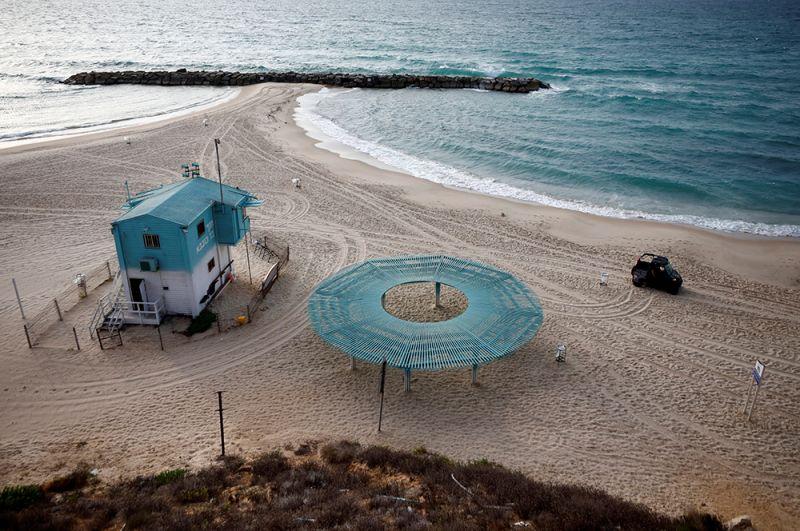 За соблюдением всеобщего карантина будет следить полиция Израиля. На фото: полицейская машина патрулирует пустынный пляж на берегу Средиземного моря.