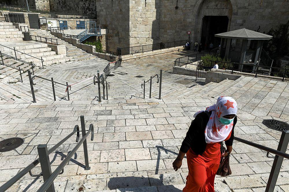 Уважительной причиной выхода из дома являются участие в различных религиозных церемониях и обрядах. На фото: женщина идет по пустынной площади в Старый город Иерусалима.
