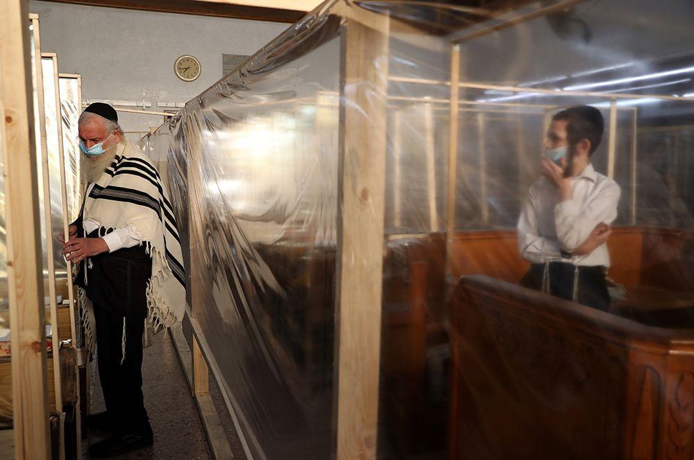 Утренняя молитва в синагоге, которая снабжена пластиковыми перегородками для защиты от коронавируса, Иерусалим.
