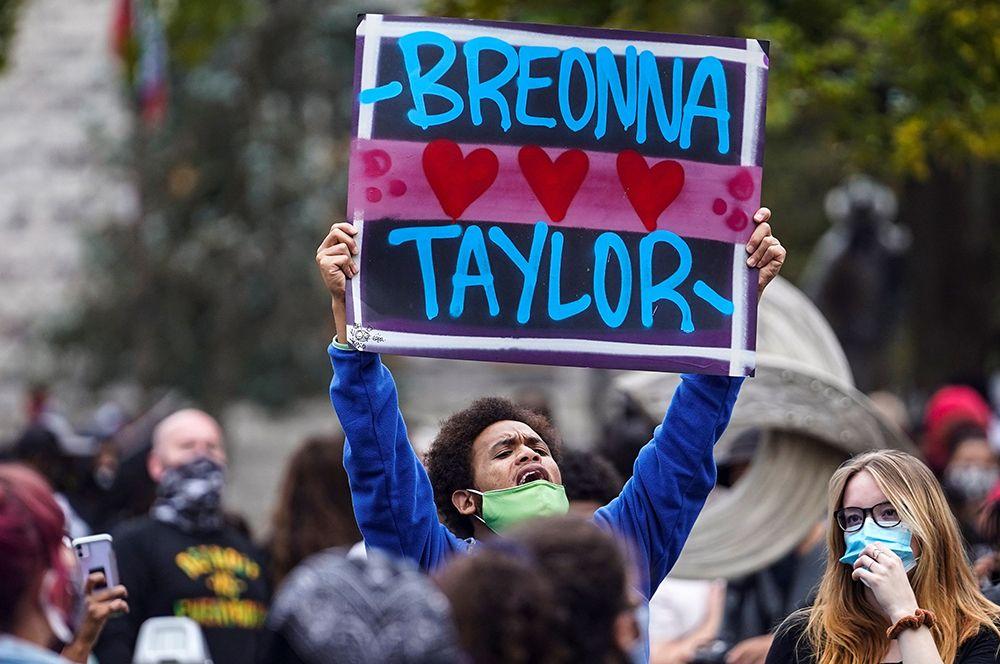 Демонстранты с плакатами во время протестов.