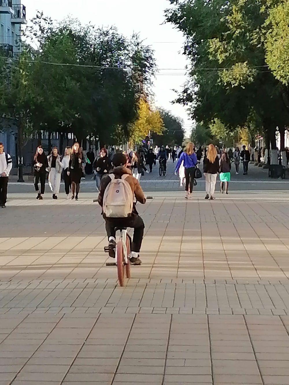Народ гуляет по центральной пешеходной улице, уже привыкнув пить кофе только на ходу.