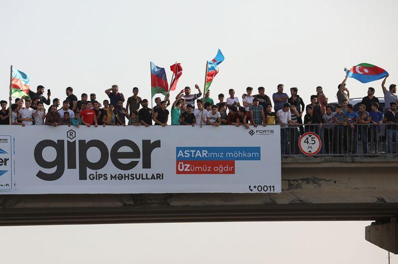 Люди собираются на мосту над автомагистралью, чтобы поприветствовать азербайджанских военных в Баку, Азербайджан.