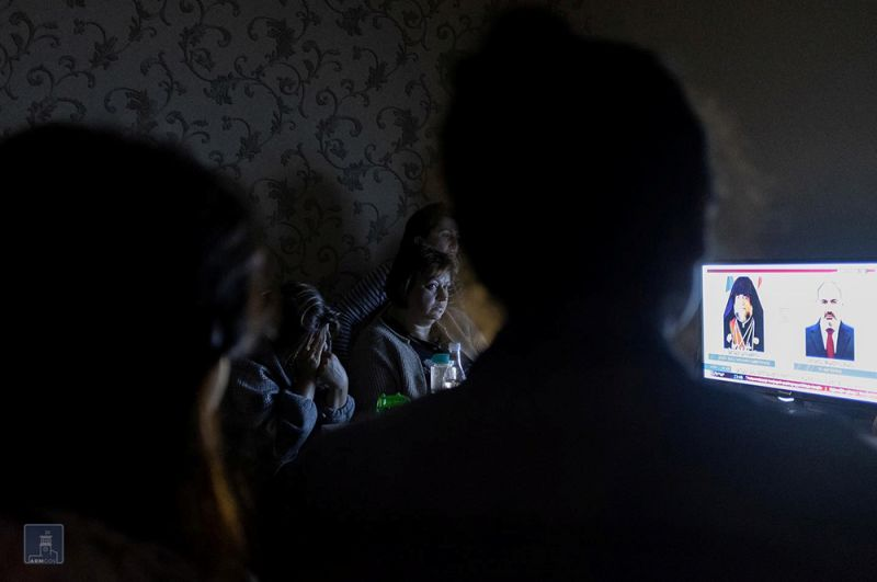 Люди смотрят телевизор в бомбоубежище в Степанакерте.