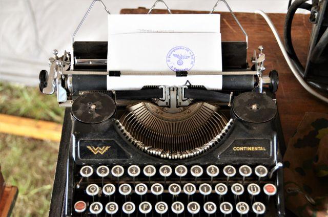 Старая нацистская пишущая машинка с бумагой, захваченная в Германии во время Второй мировой войны.