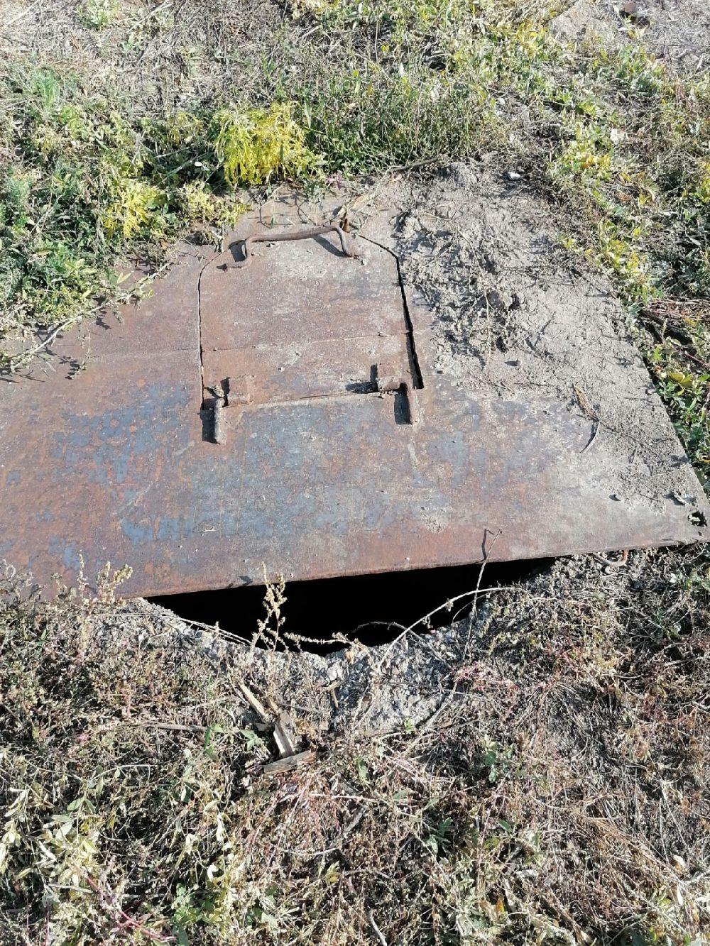 На заднем дворе сливная яма прикрыта ржавым щитом.