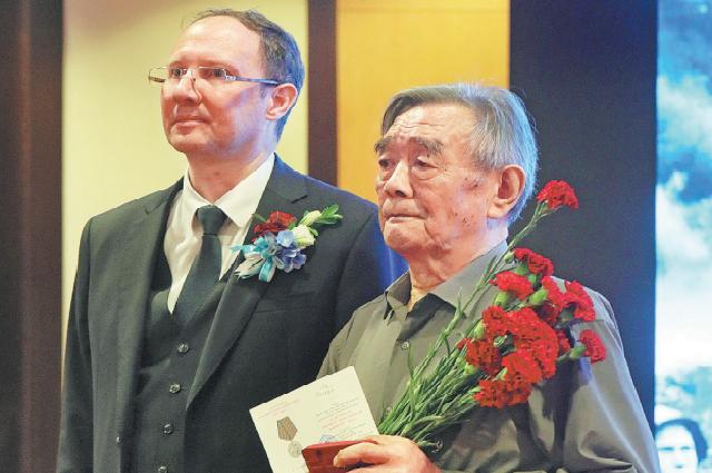 Генеральный консул России Сергей Черненко вручает медаль 79-летнему Ли Баохуа в Шэньяне, провинция Ляонин, 3 сентября.