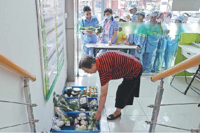 Рабочие ожидают раздачи бесплатных овощей в отделении продо- вольственного банка в Шанхае.