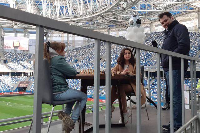Варвара Кузьмина (слева) и Эмилия Завиваева сыграли в шахматы в перерыве футбольного матча.