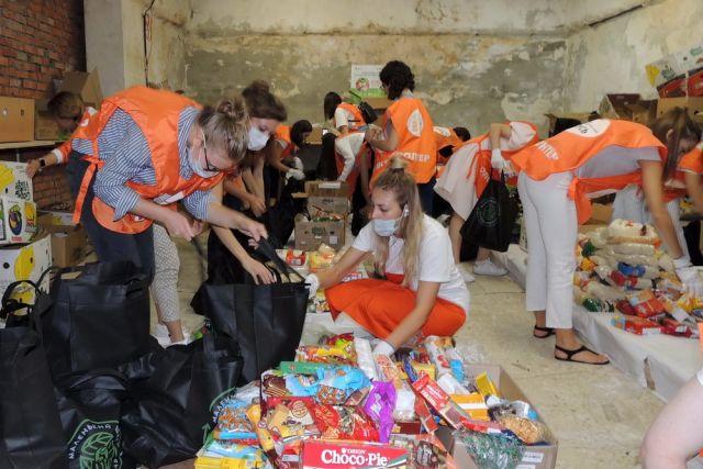Волонтёры собирают продовольственные наборы для малоимущих семей.