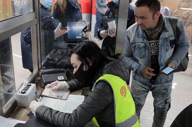 Сотрудница метрополитена выписывает штраф за несоблюдение масочного режима.
