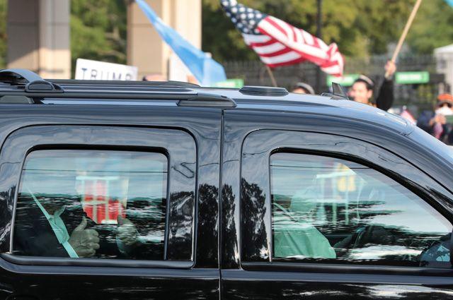 Ввоскресенье Трамп даже совершил короткую поездку наавтомобиле: проехался перед собравшимися угоспиталя сторонниками ипомахал имрукой.
