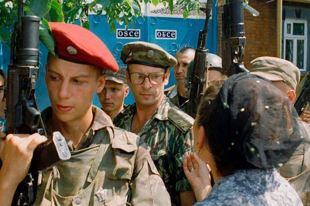 Чеченская мать обращается к командующему объединенной группой федеральных войск генерал-лейтенату Анатолию Романову (второй справа), выходящему из миссии ОБСЕ после переговоров по урегулированию кризиса в Чечне. 1995 г.