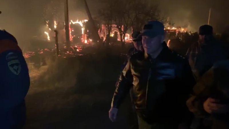 Министр МЧС России Евгений Зиничев (в центре) осматривает территорию, где пострадали жилые строения в результате пожара на территории склада хранения боеприпасов Западного военного округа в Рязанской области.