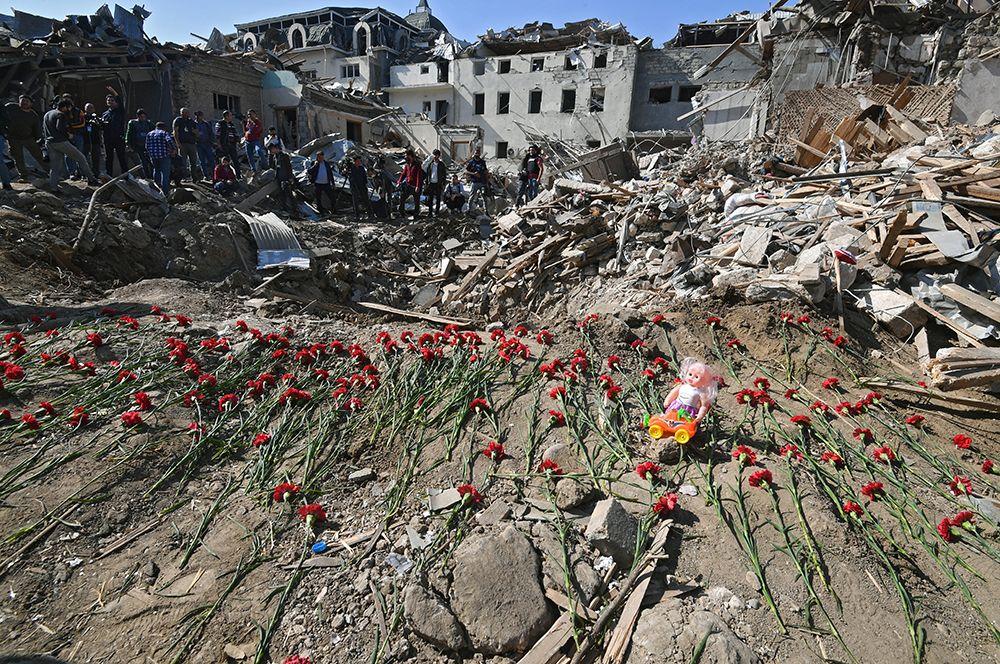 Жители города несут цветы к месту гибели людей, погибших в результате обстрела города Гянджа.