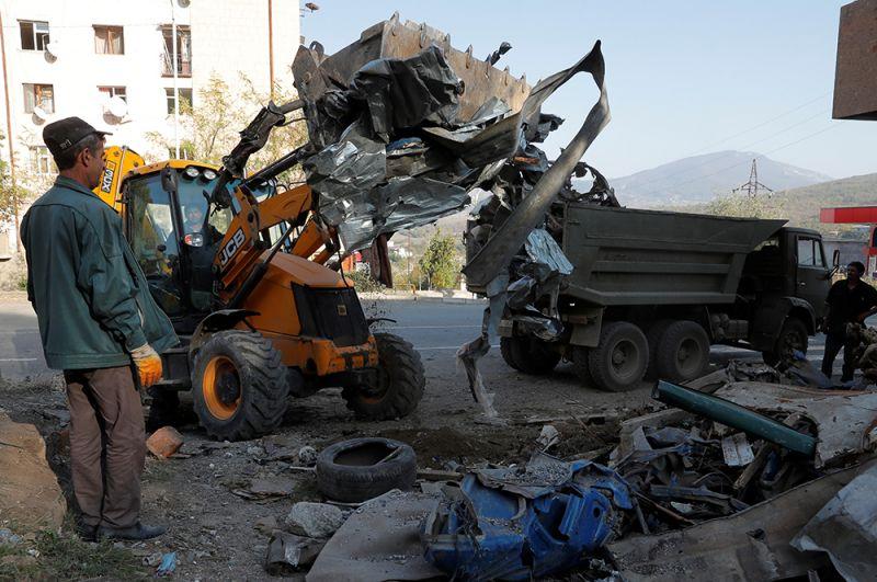 Рабочие убирают завалы после обстрелов возле жилого дома в Степанакерте.