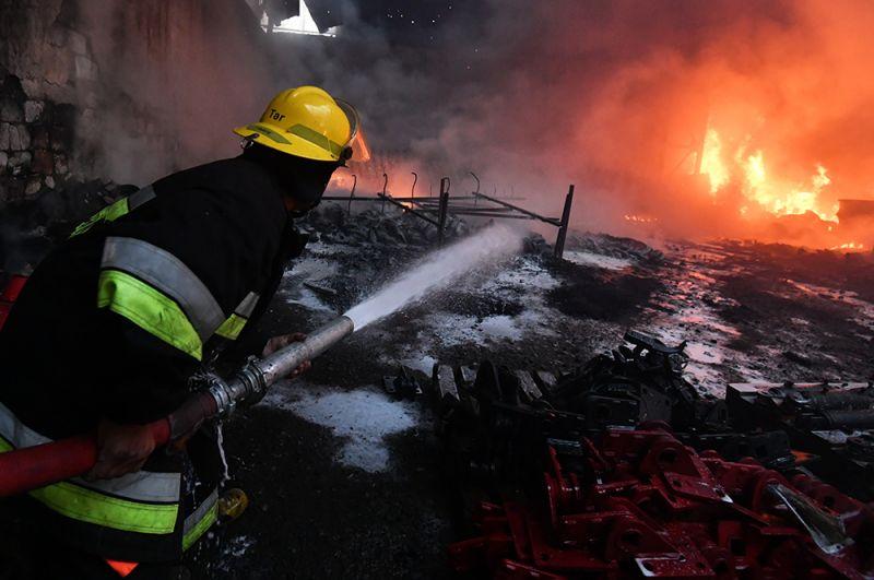 Пожарный тушит пожар на хлопковом заводе в деревне Азат Карагоинлы в Азербайджане, который возник в результате артиллерийского обстрела.