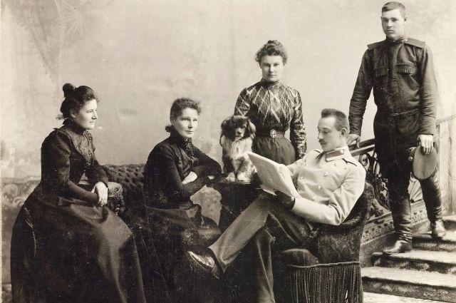 Семья штабс-капитана, офицера-воспитателя Омского кадетского корпуса Аполлона. Подкорытова. Он сидит в кресле с газетой, рядом с ним его жена Мария, его сестры Елена и Вера. На ступеньках лестницы стоит денщик.
