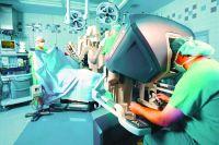 Врачи оперируют пациента при помощи робота.