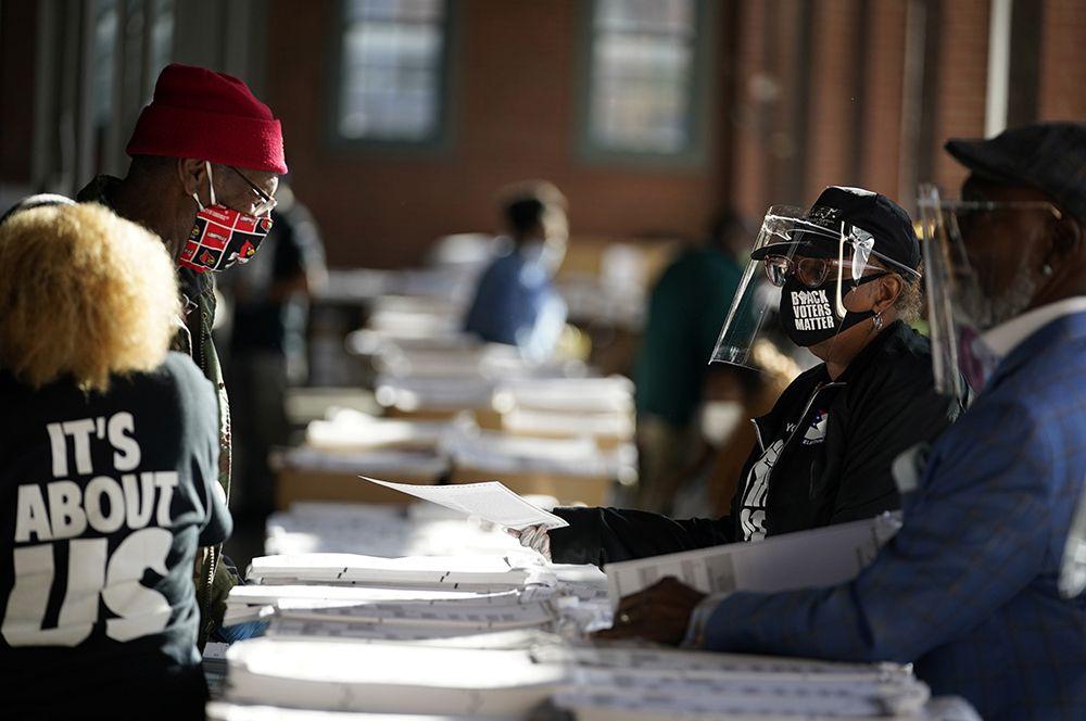 Сотрудники избирательной комиссии раздают бюллетени в Центре афроамериканского наследия во время президентских выборов в США в Луисвилле, штат Кентукки.