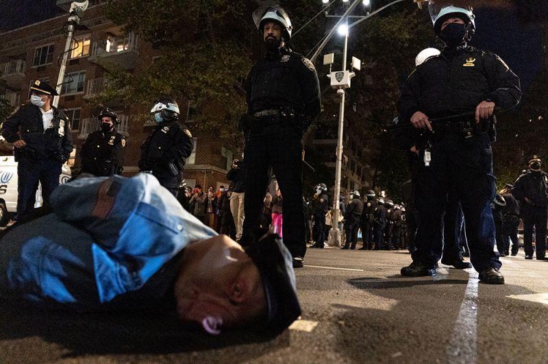 Задержанный протестующий во время акции в Нью-Йорке.