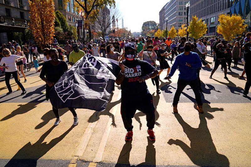 Люди танцуют на площади Black Lives Matter Plaza возле Белого дома в Вашингтоне на следующий день после объявления о победе Джо Байдена.