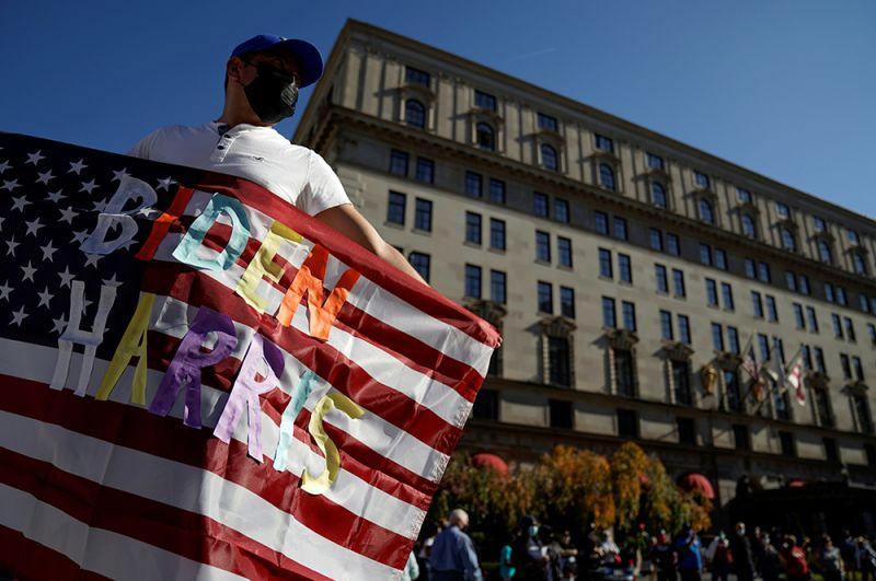 Мужчина с американским флагом с надписью «Байден Харрис» возле Белого дома в Вашингтоне.
