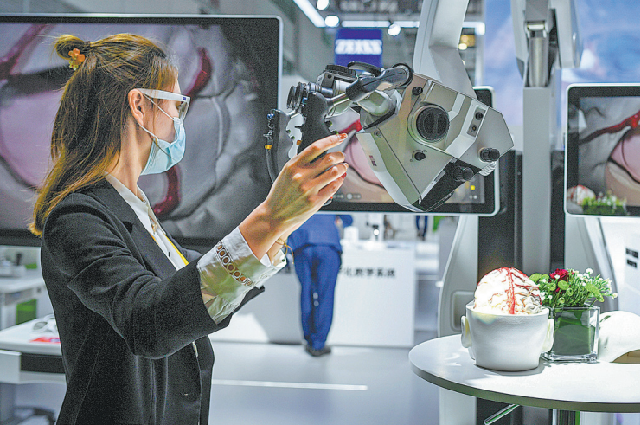 Представитель одного из участников выставки в Шанхае демонстрирует рабочий микроскоп, использующий технологию искусственного интеллекта, 7 ноября.