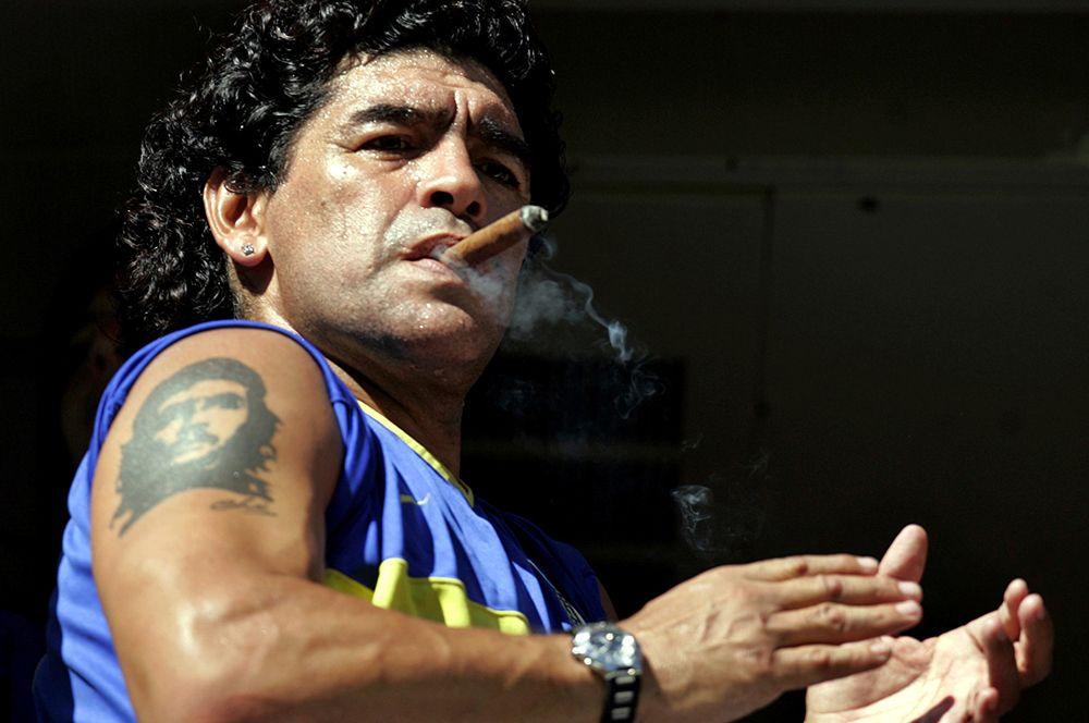 Диего Марадона курит сигару перед началом матча между «Бока Хуниорс» и «Сан-Лоренсо» на стадионе Ла-Бомбонера в Буэнос-Айресе, 2006 год.