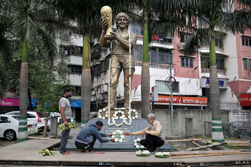 Мужчины украшают статую Марадоны цветами в Калькутте, Индия.