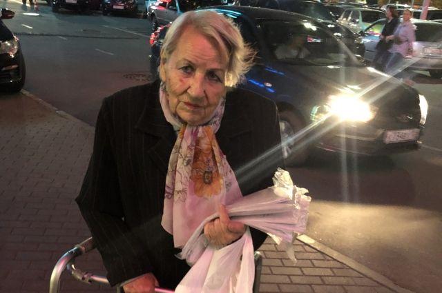 Пожилая жительница Воронежа продает свои стихотворения у торгового центра.
