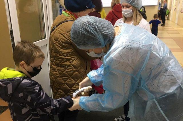 Волонтёры на протяжении нескольких часов измеряют температуру у всех, кто переступает порог поликлиники.