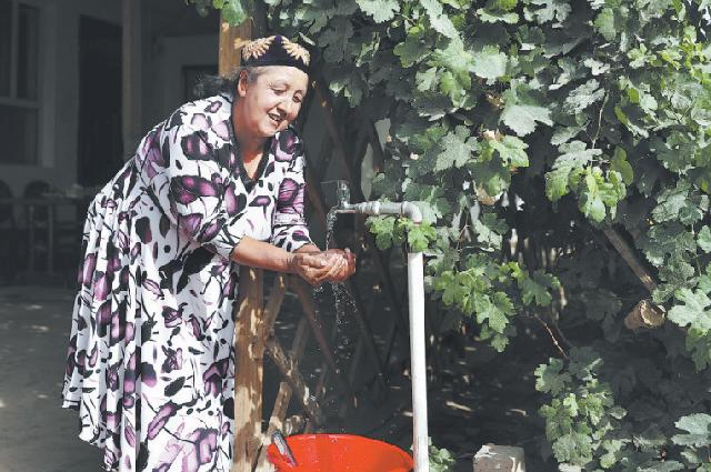 Женщина моет руки в чистой воде из-под крана, уезд Цзяши, префектура Кашгар, Синьцзян-Уйгурский автономный район.