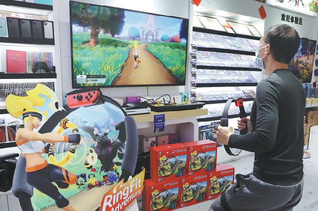 Пользователь играет в фитнес-игру Ring Fit Adventure от японской компании Nintendo в торговом центре в Пекине, октябрь 2020 г.