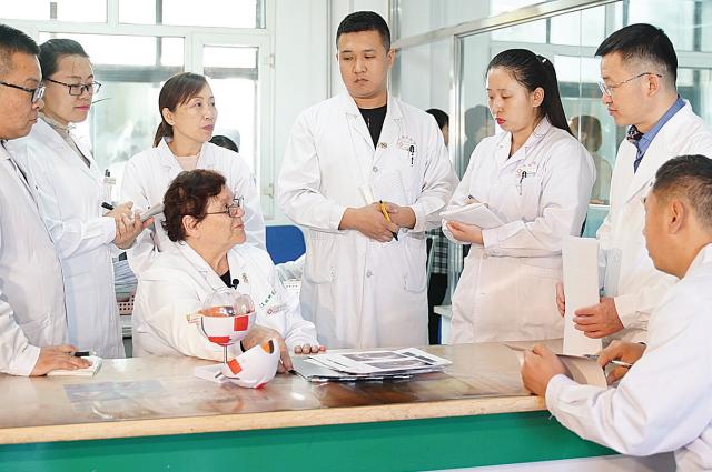 Лилия Анатольевна Попова разговаривает с молодыми врачами в офтальмологической клинике г. Дацин, провинция Хэйлунцзян.
