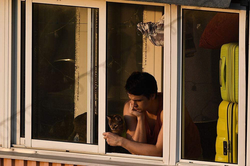 Молодой человек на балконе многоквартирного дома в Москве во время режима самоизоляции.