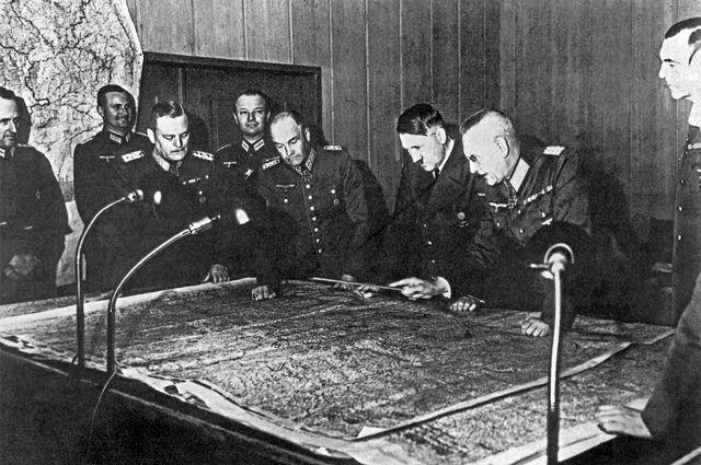 Генерал-фельдмаршал В. Кейтель, генерал-полковник В. фон Браухич, А. Гитлер, генерал-полковник Ф. Гальдер (слева направо на первом плане) около стола с картой во время совещания Генерального штаба.