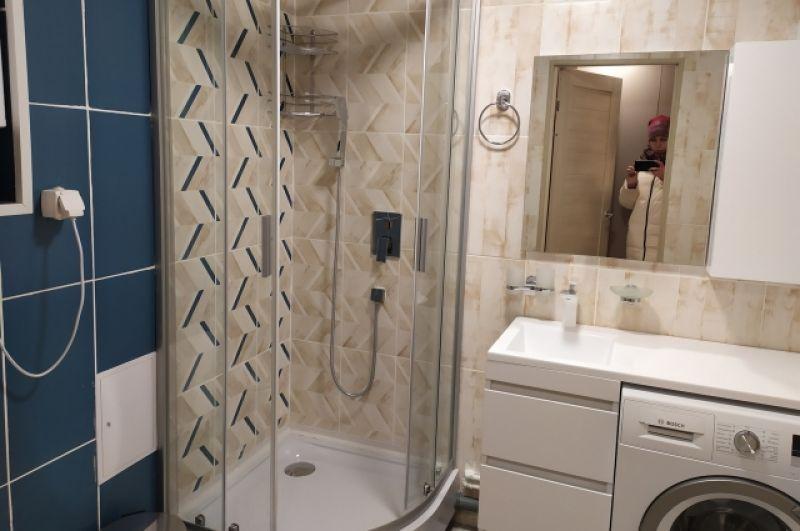 В ванной душевая кабина и стиральная машина-автомат.