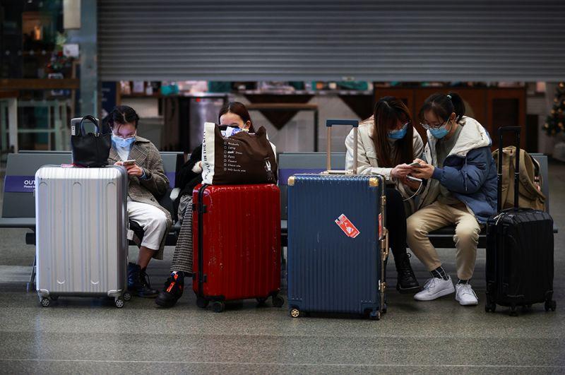 Путешественники с чемоданами в терминале аэропорта.