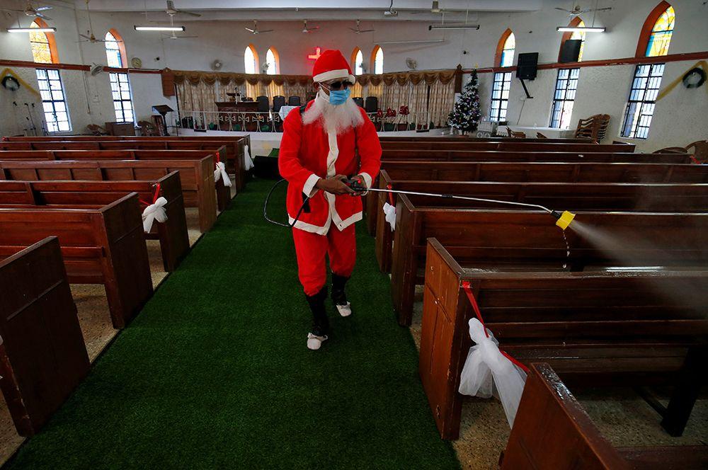 Дезинфекция церкви перед рождественскими праздниками в Ахмедабаде, Индия.
