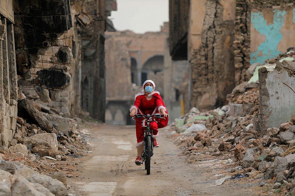 Женщина в костюме Санта-Клауса в Мосуле, Ирак.
