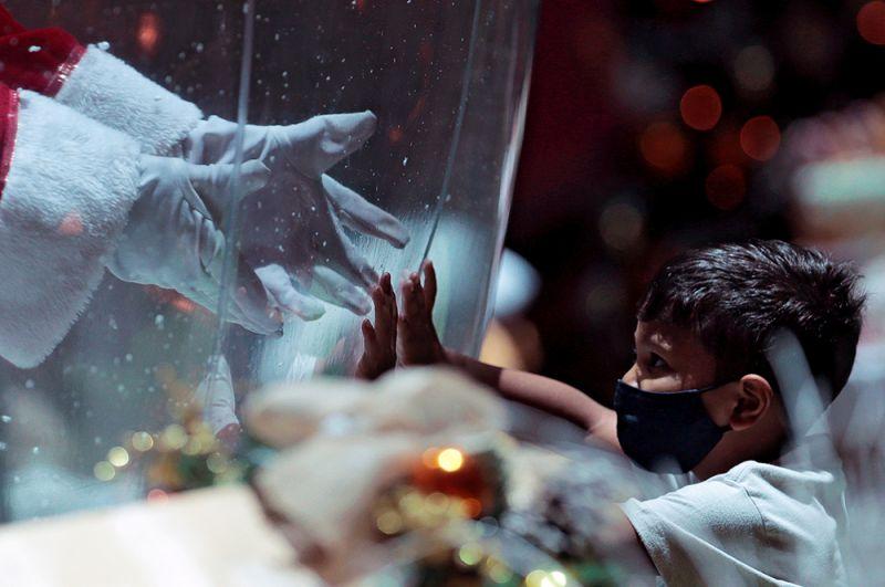 Санта-Клаус приветствует ребенка в торговом центре в Бразилиа, Бразилия.