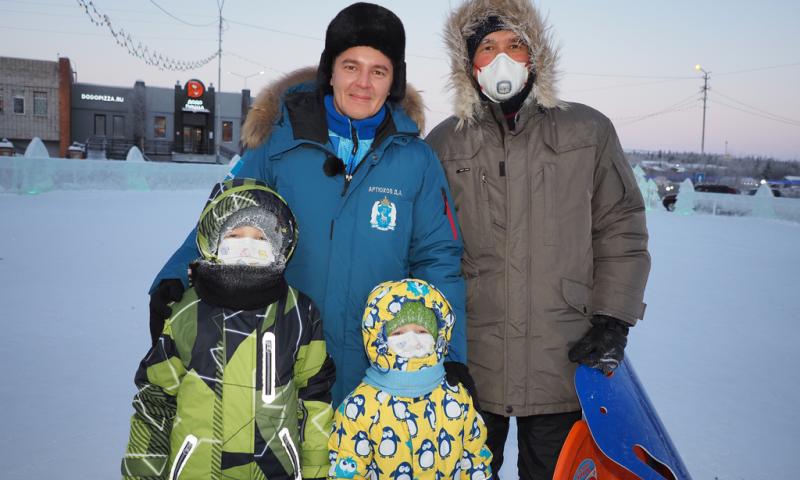 В ледовом городке на площади В. Нака гуляют семьи с детьми.