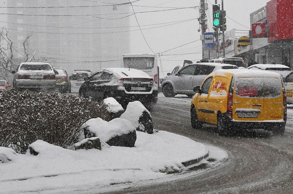 Автомобильное движение во время снегопада во Владивостоке.
