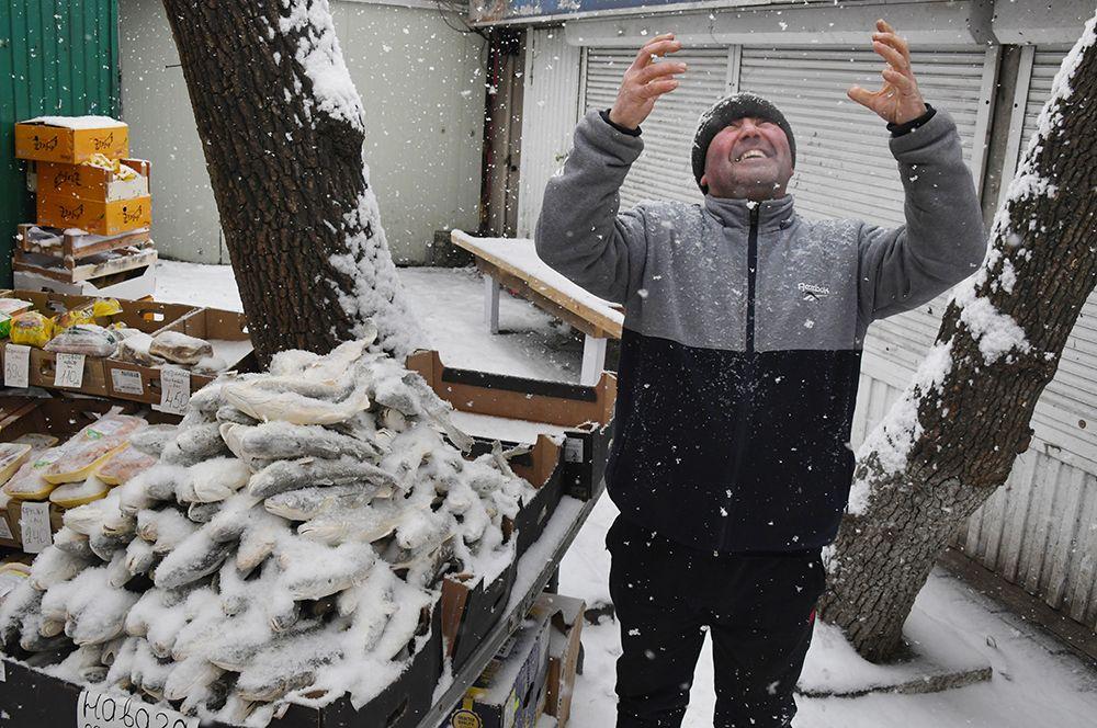 Мужчина, торгующий рыбой, во время снегопада во Владивостоке.
