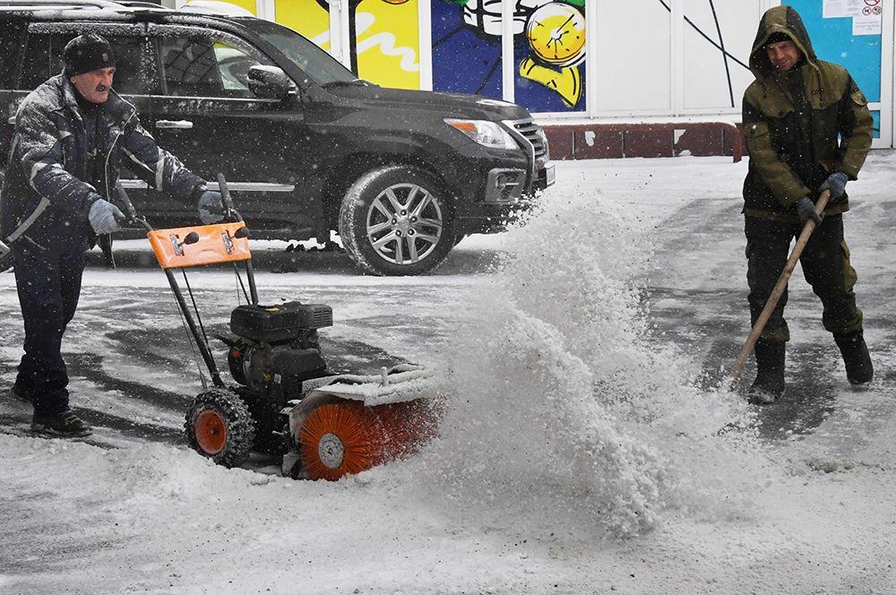 Мужчины убирают снег во время снегопада во Владивостоке.
