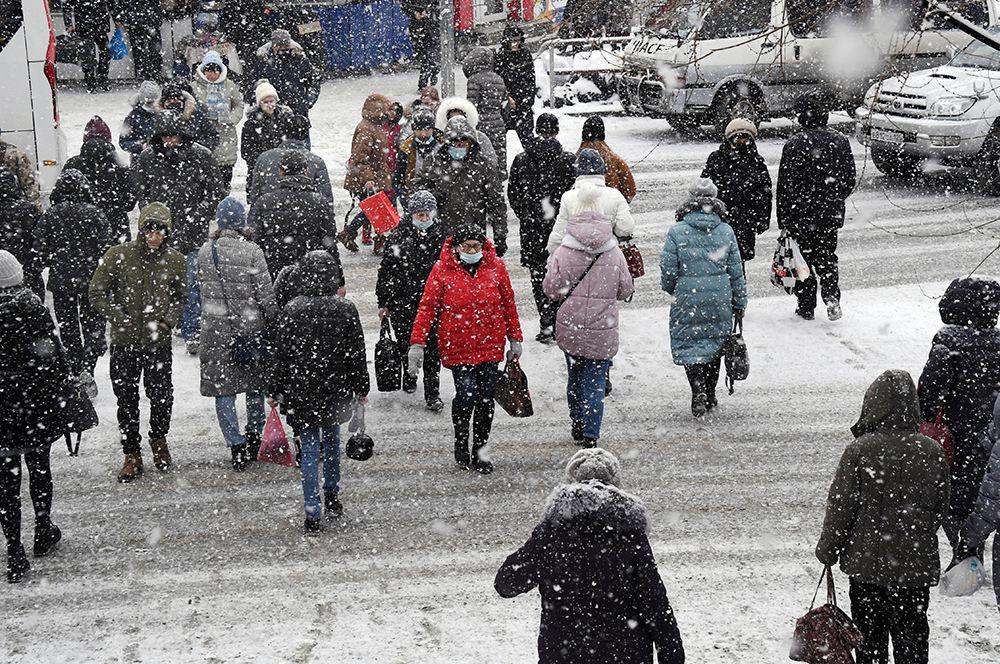 Прохожие во время снегопада во Владивостоке.