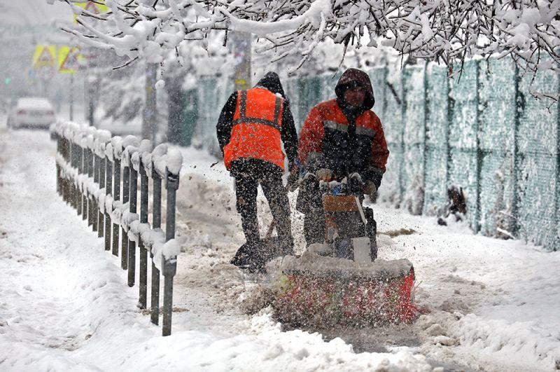 Уборка снега во время снегопада на улице Краснодара.
